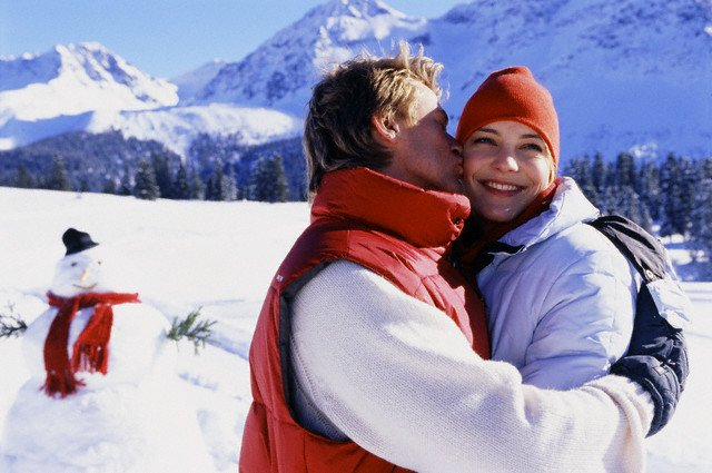 Young Couple Cuddling in Winter Landscape --- Image by © A. Inden/zefa/Corbis